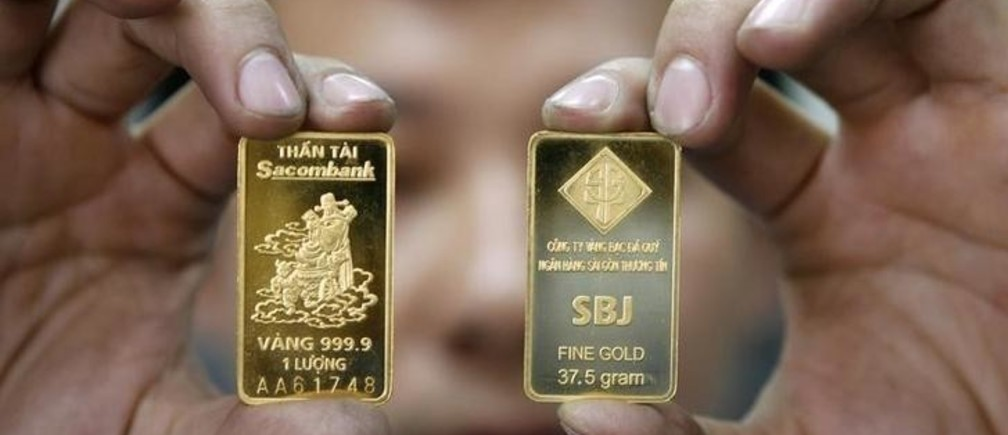 A man displays gold bars at the Sacombank gold bar factory in Vietnam's southern Ho Chi Minh city January 22, 2010. REUTERS/Kham (VIETNAM - Tags: BUSINESS)