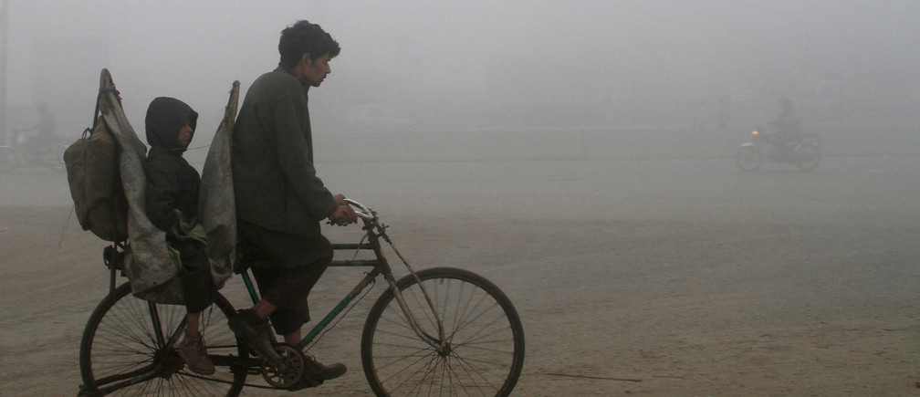 A man and his child ride on a bicycle in heavy smog in Lahore, Pakistan January 26, 2018. REUTERS/Mohsin Raza - RC1DA3DF7DC0