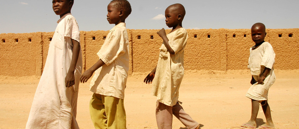 Darfur refugees walk past their school in the Gaga refugee camp in eastern Chad in this January 26, 2006 file photo. Chad's President Idriss Deby held a victory rally attended by thousands of supporters in the sun-baked capital N'Djamena on April 15, 2006 but many nervous residents feared rebels fighting to topple him may return. Insurgents bent on ending Deby's near 16-year rule over one of the world's poorest countries launched their most daring strike yet on Thursday, slipping into the dusty city at dawn before loyalist forces fought them off. Chad, which says the fighting killed more than 300 people,  has accused Sudan of backing the rebels and cut diplomatic ties with Khartoum on Friday, shutting its borders and threatening to stop sheltering refugees from Sudan's Darfur region. Picture taken January 26, 2006. REUTERS/Claire Soares/Files - GM1DSJXCVSAA