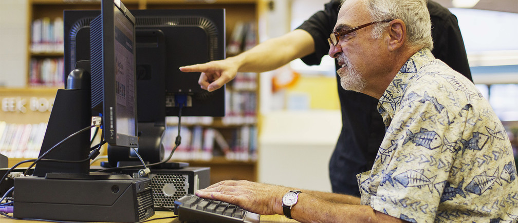 Librarian Bertrand Bobis  (L) teaches a senior citizen how to use a Facebook account during a class at a branch of the New York Public Library in New York August 13, 2012. Seniors, some in their 90s, could soon be making new friends on Facebook thanks to New York libraries offering classes to help the elderly learn, or brush up their social network skills. REUTERS/Lucas Jackson (UNITED STATES - Tags: SOCIETY SCIENCE TECHNOLOGY EDUCATION) - RTR36TKI