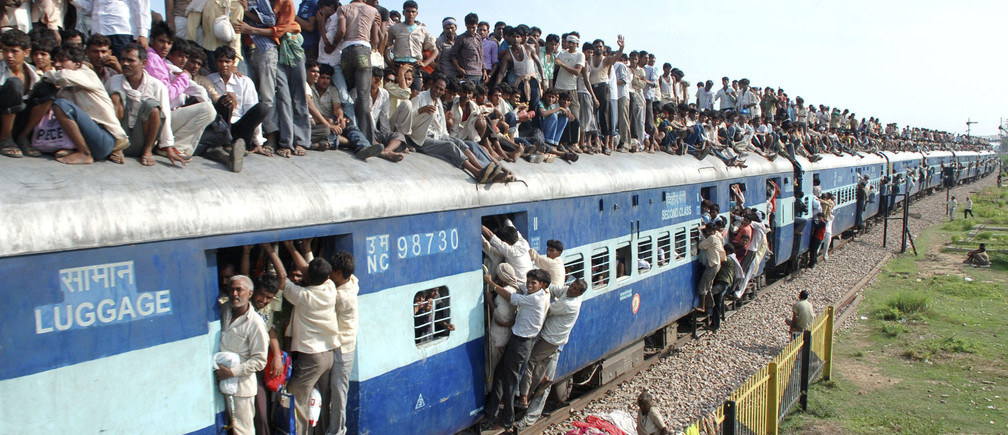 """Hindu devotees travel on a crowded passenger train to take part in the """"Guru Purnima"""" festival in Goverdhan town near the northern Indian city of Mathura July 24, 2010. Guru Purnima is observed to pay respects to one's """"guru"""" or teacher who symbolises the Hindu Trinity of Brahma, Vishnu and Mahesh, believed to be the creators of the universe and will be celebrated on Sunday. REUTERS/K. K. Arora (INDIA - Tags: SOCIETY RELIGION TRANSPORT) - RTR2GONX"""