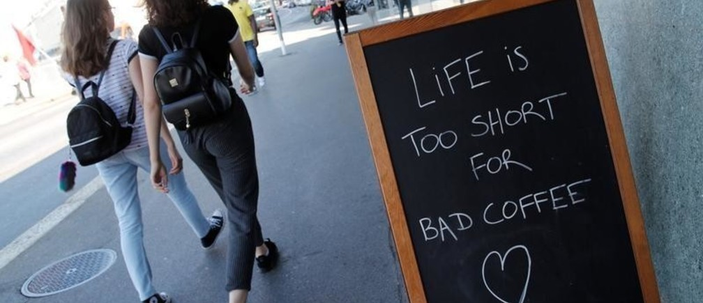 "A sign reads, ""Life is too short for bad coffee"", outside the Coffee Project in Lausanne, Switzerland, July 19, 2018."