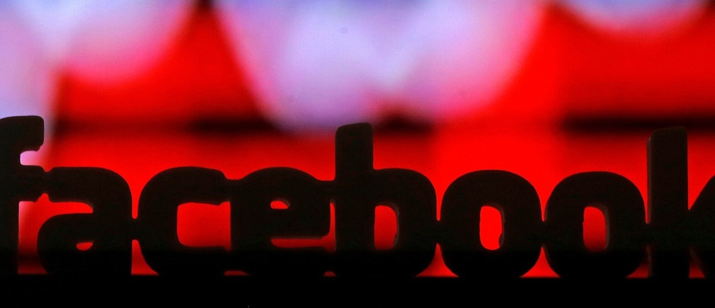 A 3D printed Facebook logo is seen in front of a displayed stock graph