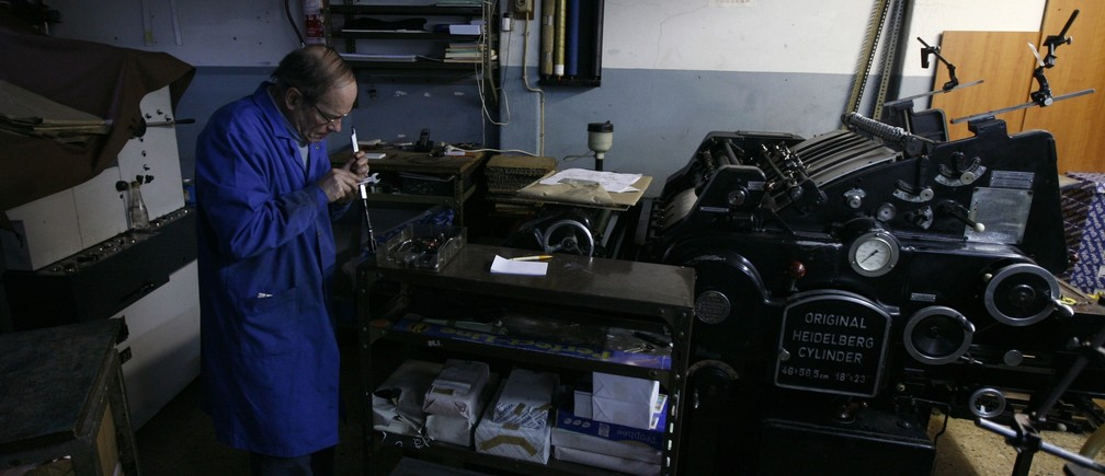 Retiree Victor Goncalves, 67, works in a printing shop at the Alfama neighborhood in Lisbon February 14, 2012. Goncalves receives a state pension of 400 euros ($525) each month but still needs to run his printing shop to support himself. Three years ago, he used to have 280 customers daily but today, he only sees 30 customers every day.   REUTERS/Rafael Marchante (PORTUGAL - Tags: SOCIETY BUSINESS EMPLOYMENT) - RTR2XUSU