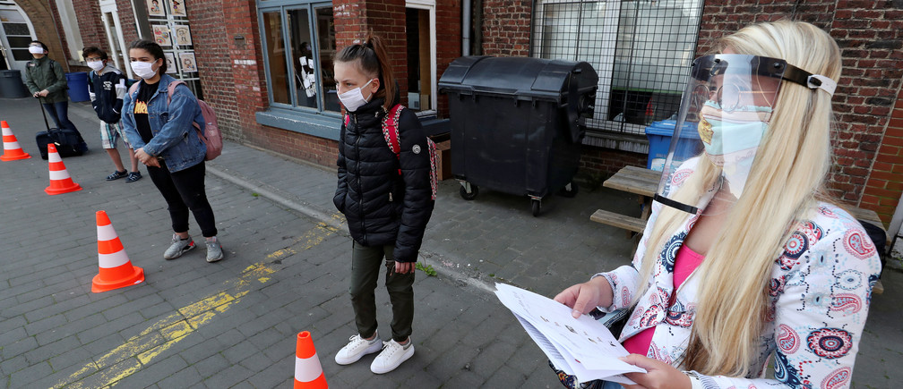 Students wearing protective face masks keep social distancing as they arrive a francophone primary school during its reopening in Jumet, as a small part of Belgian children head back to their schools with new rules and social distancing measures, during the outbreak of the coronavirus disease (COVID-19), in Jumet, Belgium, May 18, 2020. REUTERS/Yves Herman - RC2VQG99GB6P