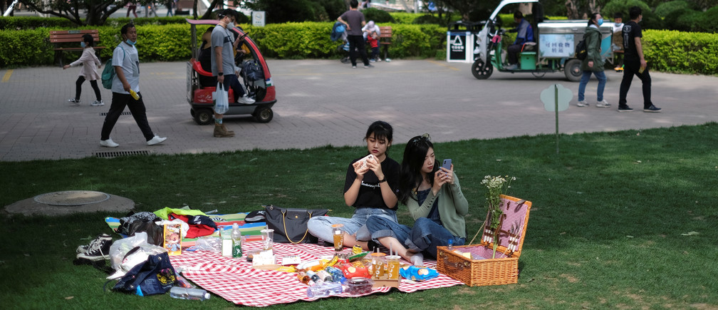 Women use their cellphones while sitting on a picnic blanket at Sun Park during Labour Day holiday, following an outbreak of the coronavirus disease (COVID-19), in Beijing, China May 5, 2020. REUTERS/Carlos Garcia Rawlins - RC2EIG9BMJD3