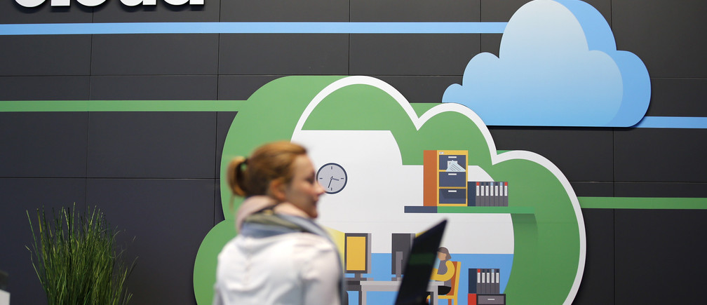 A women holds her laptop as she walks in front of a cloud computing logo at the booth of IBM during preparations for the CeBIT trade fair in Hanover, March 9, 2014.