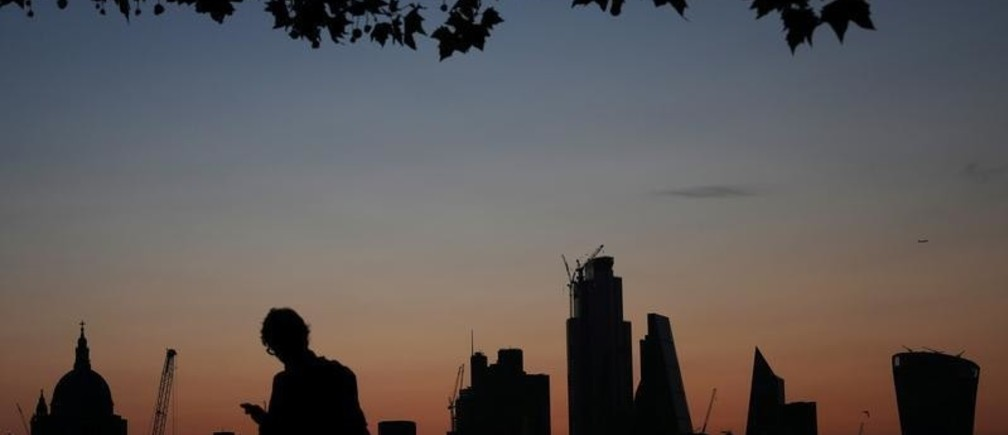 A man walks past the city of London financial district as dawn breaks in London, Britain August 20, 2019. REUTERS/Hannah McKay - RC18BB49F780