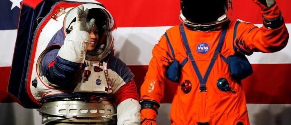 Advanced Space Suit Engineer at NASA Kristine Davis wears the xEMU prototype space suit next to lead engineer Dustin Gohmert wearing the Orion crew survival spacesuit prototype for the next astronaut to the moon by 2024, during a presentation at NASA headquarters in Washington, U.S., October 15, 2019. REUTERS/Carlos Jasso - RC1E81D397F0