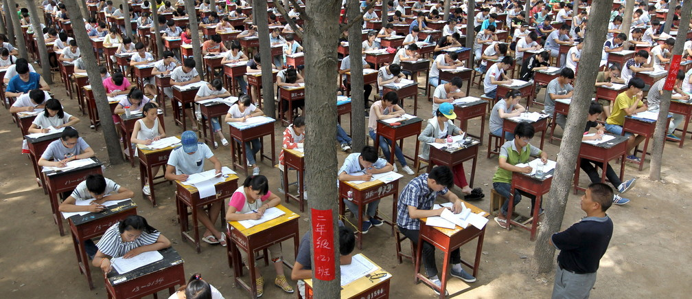 Students take term final exam among trees outside a classroom building at a middle school in Xinxiang, Henan province, China, July 3, 2015. The school set up the exam outdoor to create a more comfortable environment for the students, according to local media. Picture taken July 3, 2015. REUTERS/Stringer CHINA OUT. NO COMMERCIAL OR EDITORIAL SALES IN CHINA. - GF10000148188