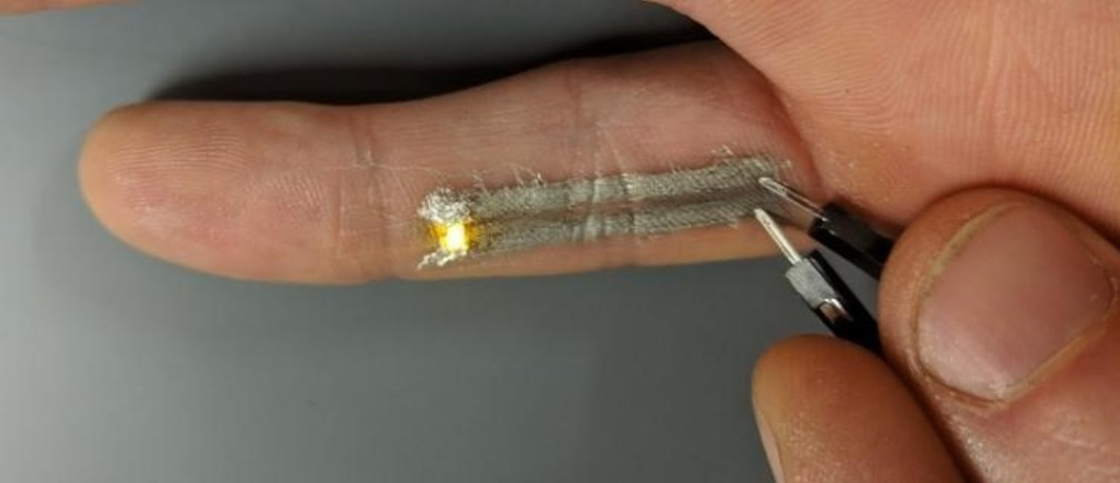 Two electronically active leads directly printed along the underside of Duke graduate student Nick Williams's pinky successfully light up an LED when a voltage is applied.