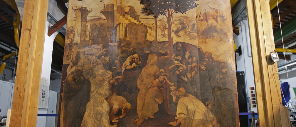 The Adoration of the Magi, a massive painting that Leonardo da Vinci started in 1481 at the age of 29 but abandoned a year later, leaving it in various stages of conception and development, is unveiled in Florence September 23, 2014. The painting on wood, measuring about 2.5 by 2.5 meters (8.2 by 8.2 feet) depicts the three wise men who paid tribute to the infant Jesus in Bethlehem, but it also includes a riot of human figures, battling horses, architectural designs, landscapes and skies. Done on 10 slabs of wood glued together, it has blank areas, areas with under-drawings, and sections in advanced stages. The current restoration project has revealed many previously hidden details, facial expressions and subtleties of light and shadow. After the wood backing of the painting is restored, it is due to return to a special room in the Uffizi, where it will be on display with two other Leonardo works. To match Feature ART-ITALY/LEONARDO     Picture taken September 23, 2014.  REUTERS/Max Rossi   (ITALY - Tags: SOCIETY) - GM1EA9O1SGD02