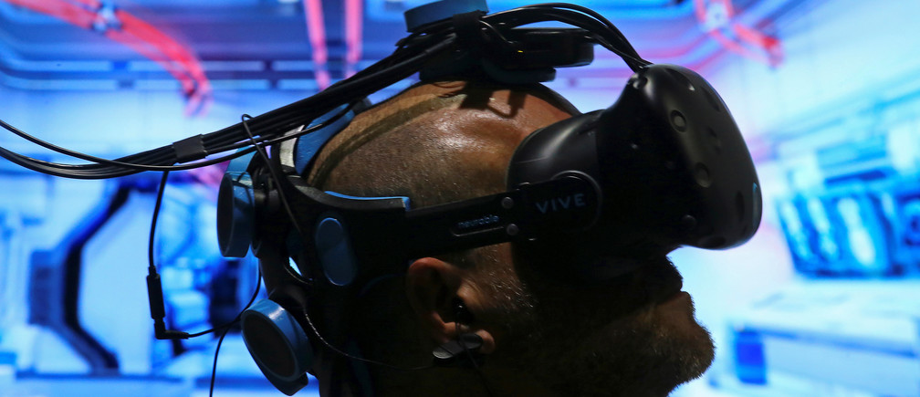 Pablo Holcer tests out a virtual reality system made by Neurable that allows the user to control with their thoughts as the EEG headset interprets thoughts into actions in the VR environment at SIGGRAPH 2017 in Los Angeles, California U.S. July 31, 2017.  REUTERS/Mike Blake     TPX IMAGES OF THE DAY - RTS19WS4