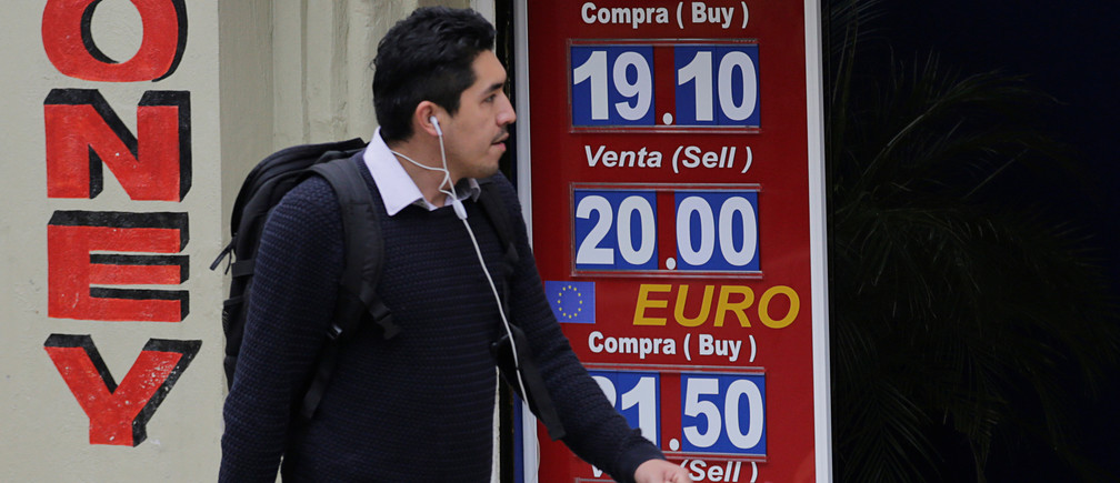 A man walks past a board displaying the exchange rates of Mexican peso against the U.S. dollar and the Euro at a foreign exchange house in Mexico City, Mexico November 17, 2016. REUTERS/Henry Romero - RTX2U57M