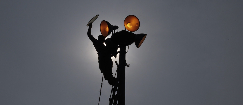 A worker is silhouetted as he repairs streetlights at a park in Lahore November 21, 2011. REUTERS/Mohsin Raza   (PAKISTAN - Tags: BUSINESS SOCIETY EMPLOYMENT TPX IMAGES OF THE DAY) - GM1E7BL1J7901