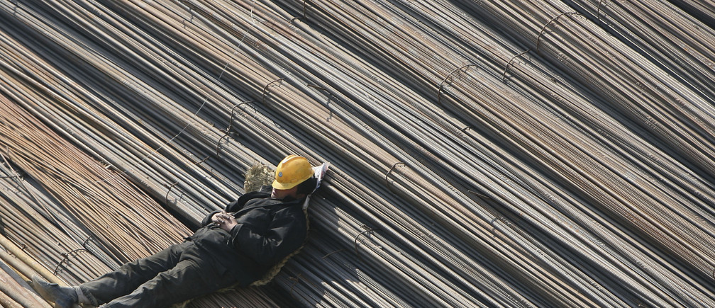 A labourer takes a nap on reinforcement bars at a construction site in Qingdao, Shandong province March 5, 2008. Chinese Premier Wen Jiabao warned on Wednesday that overheating remains his nation's top economic foe even as global growth softens, vowing a tough fight against price rises and feverish investment. Picture taken March 5, 2008. REUTERS/Stringer(CHINA) CHINA OUT - GM1E4360VUG01