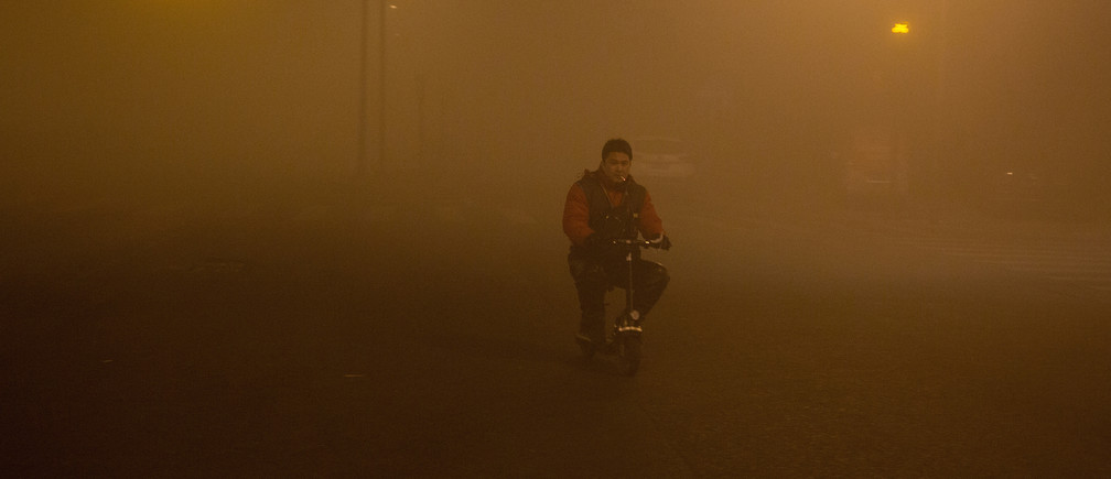 A man smokes as he rides in smog during polluted day in Beijing, China, December 20, 2016. REUTERS/Stringer ATTENTION EDITORS - THIS IMAGE WAS PROVIDED BY A THIRD PARTY. EDITORIAL USE ONLY. CHINA OUT. NO COMMERCIAL OR EDITORIAL SALES IN CHINA. - RC1A854E6120