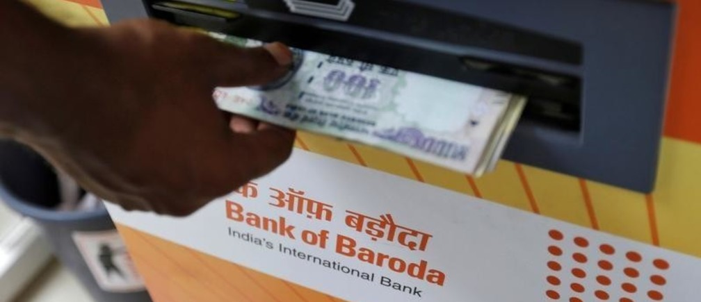 A customer withdraws money from a Bank of Baroda automated teller machine (ATM) in Mumbai, India