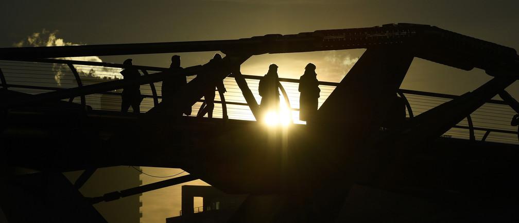 Commuters make their way across the Millennium Bridge as the sun rises over London, Britain November 30, 2016.