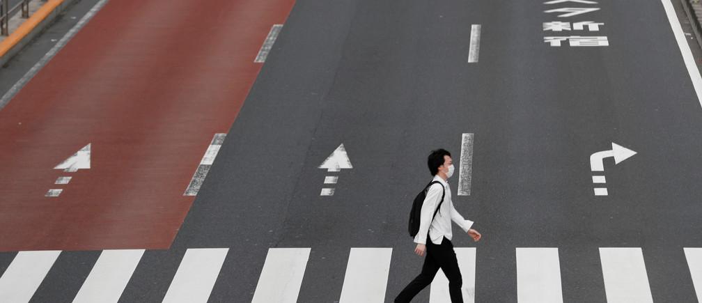Un hombre con una máscara facial protectora cruza una calle en Shinjuku, tras el brote de la enfermedad coronavirus (COVID-19), Tokio, Japón, 4 de mayo de 2020.