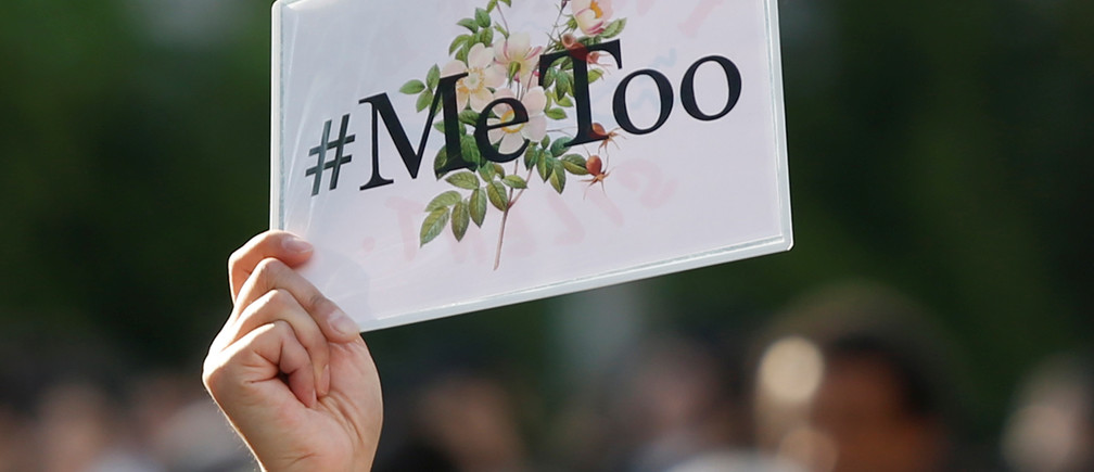 """A protester raises a placard reading """"#MeToo"""" during a rally against harassment at Shinjuku shopping and amusement district in Tokyo, Japan, April 28, 2018. Picture taken April 28, 2018. REUTERS/Issei Kato - RC19441C57D0"""