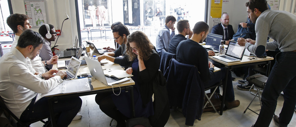"""Entrepreneurs work at their computer laptops at the so-called """"incubator"""" of French high-tech start-ups """"Numa"""" in Paris, France, March 11, 2016.   REUTERS/Charles Platiau  - RTSAD72"""