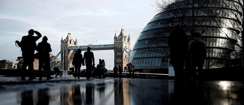 Pedestrians walk near City Hall and Tower Bridge in London, Britain January 24, 2016.