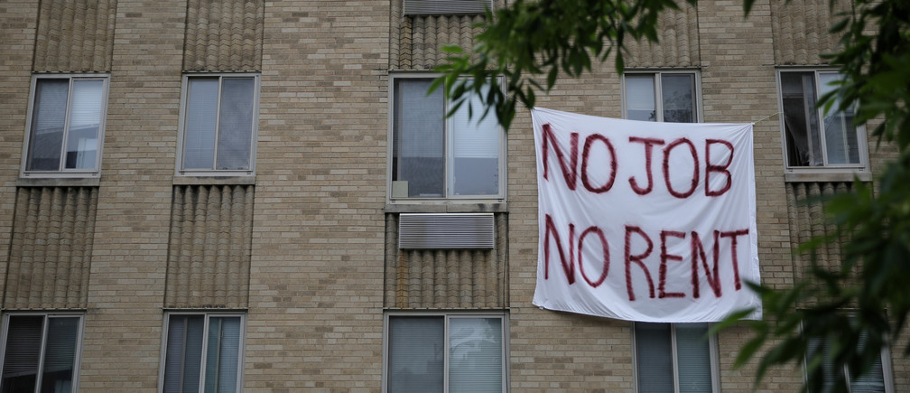 Makeshift sheets displaying messages of protest contesting the ability to pay for rent hang in the window of an apartment building in the Columbia Heights neighborhood in Washington, U.S., May 18, 2020. REUTERS/Tom Brenner     TPX IMAGES OF THE DAY - RC27RG95JZX4