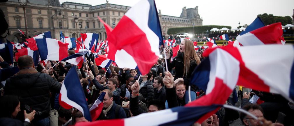 Supporters of President Elect Emmanuel Macron celebrate near the Louvre museum after results were announced in the second round vote of the 2017 French presidential elections, in Paris, France May 7, 2017. REUTERS/Benoit Tessier - RTS15K4F