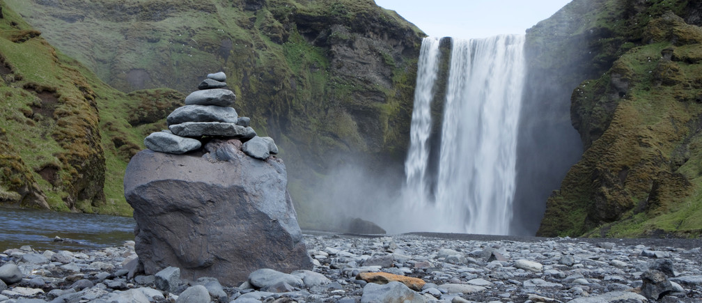 A pile of rocks stand in front of a waterfall in Skogarfoss, Iceland May 28, 2011. REUTERS/Lucas Jackson (ICELAND - Tags: ENVIRONMENT TRAVEL) - GM1E75T04MM01