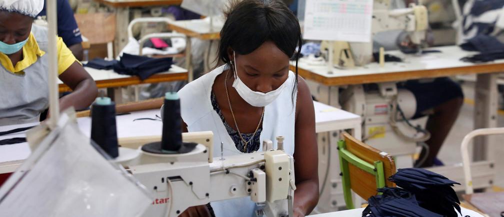 Trabajadores hacen máscaras faciales en un fabricante local de ropa después de que éste cambiara parte de su producción de la exportación de ropa a la fabricación de máscaras protectoras, en medio del brote de la enfermedad coronavirus (COVID-19), en Puerto Príncipe, Haití, el 21 de abril de 2020.