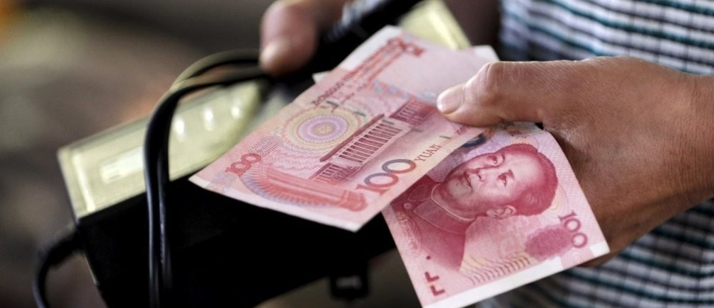 A customer holds a 100 Yuan note at a market in Beijing, August 12, 2015. China shocked global markets on Tuesday by devaluing its currency after a run of poor economic data, a move it billed as a free-market reform but which some experts suspect could be the beginning of a longer-term slide in the exchange rate.