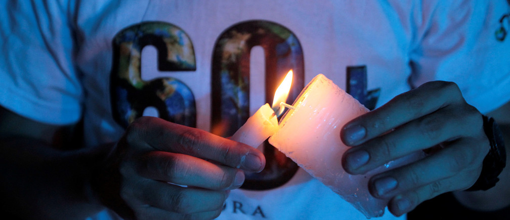 "A participant lights a candle to form a ""60+"" sign during the Earth Hour environment campaign in Medellin, Colombia March 24, 2018. REUTERS/Fredy Builes - RC1FD0364300"