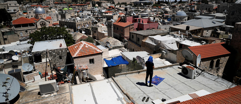 A Muslim worshipper prays during Ramadan on a roof inside Jerusalem's Old City due to the coronavirus disease (COVID-19) restrictions around the country. REUTERS/Ammar Awad     TPX IMAGES OF THE DAY - RC2OFG9IFL9F