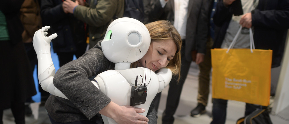 A woman embraces humanoid robot Pepper at the world's biggest computer and software fair CeBit in Hanover, Germany, March 14, 2016.  REUTERS/Nigel Treblin - LR1EC3E11MITJ