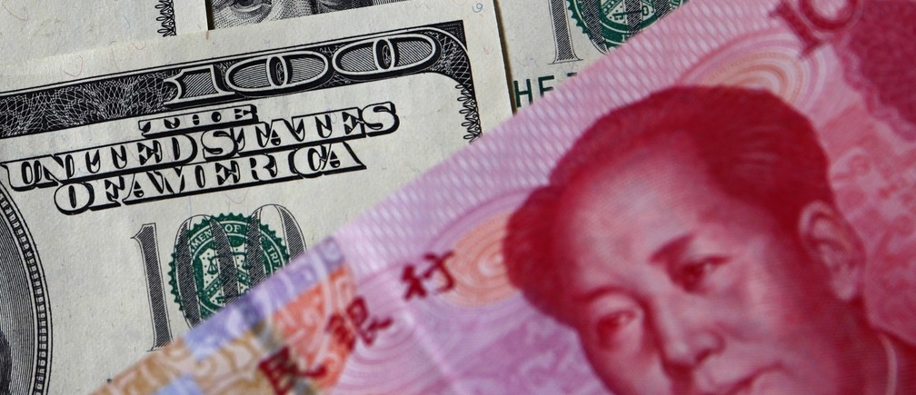 A 100 yuan banknote (bottom) is placed next to U.S. $100 banknotes in this picture illustration taken in Beijing, November 1, 2010. China will have to let the yuan rise further to reflect its robust economic growth amid growing fund inflows fanned by a loose U.S. monetary policy, an influential Chinese economist said in remarks published on Thursday. Picture taken November 1, 2010. REUTERS/Petar Kujundzic (CHINA - Tags: POLITICS BUSINESS) - RTXURR1