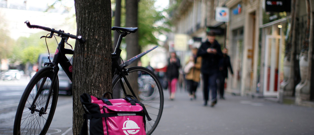 A bicycle and a delivery bag with the logo of Foodora, a Berlin-based online food delivery company, part of the emerging 'gig economy' is seen in Paris, France, April 6, 2017. Picture taken April 6, 2017. REUTERS/Gonzalo Fuentes - RC166096A2C0