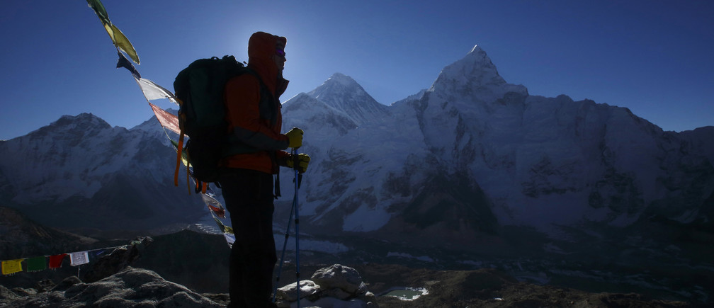 A trekker stands in front of Mount Everest, which is 8,850 meters high (C), at Kala Patthar in Solukhumbu District May 7, 2014.