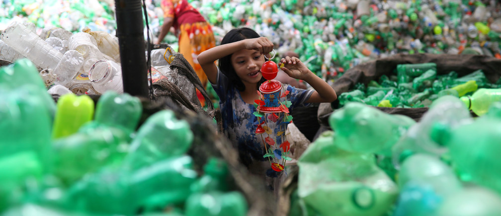 A girl plays with a toy found in a plastic recycling factory in Dhaka, Bangladesh, July 8, 2019.