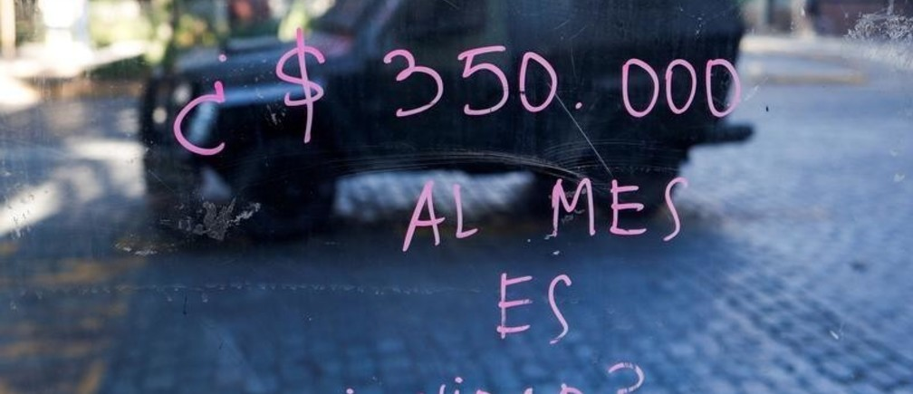 "A painted glass reading ""350.000 (Chilean peso) a month is dignity?"" reflects an armored vehicle during a protest at Providencia, a wealthy neighborhood, in Santiago, Chile November 6, 2019.  REUTERS/Jorge Silva REFILE - CORRECTING CURRENCY - RC2X5D9X82GM"