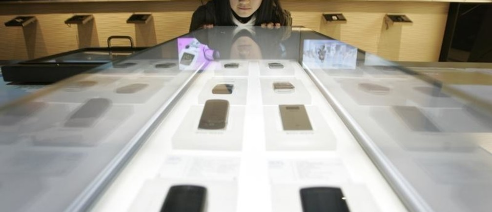 A student looks at Samsung mobile phones displayed at a showroom of Samsung Electronics, one of the subsidiary companies of Samsung Group, in Seoul December 6, 2007. The Samsung Group runs hospitals where Koreans are born, apartments for raising families, funeral halls for deaths and just about everything else for in between. Picture taken December 6, 2007. To match feature KOREA-SAMSUNG/   REUTERS/Han Jae-Ho (SOUTH KOREA) - GM1DWTYXVIAA