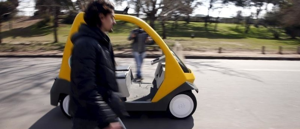 A man walks next to a prototype of an autonomous electric vehicle during its presentation in Buenos Aires, August 19, 2015. The autonomous vehicle, the first of its kind developed in Argentina, is able to fulfill the main functions of mobility of a traditional car but autonomously through the use of artificial intelligence that enables it to detect their surroundings and move without human intervention.   REUTERS/Marcos Brindicci - RTX1OUDA