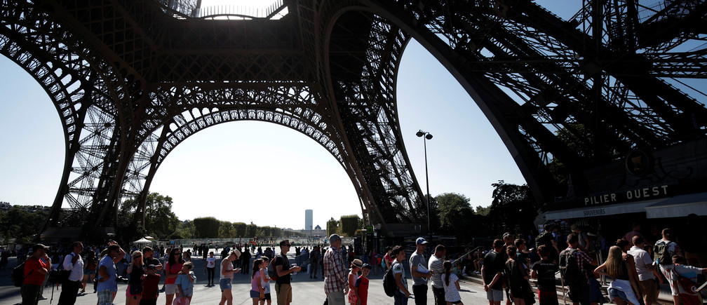 People stand in line at an information booth following the closure of the Eiffel Tower as part of a strike by employees over lengthening queues during the peak summer tourist season in Paris, France, August 2, 2018.  REUTERS/Benoit Tessier - RC11F096E930