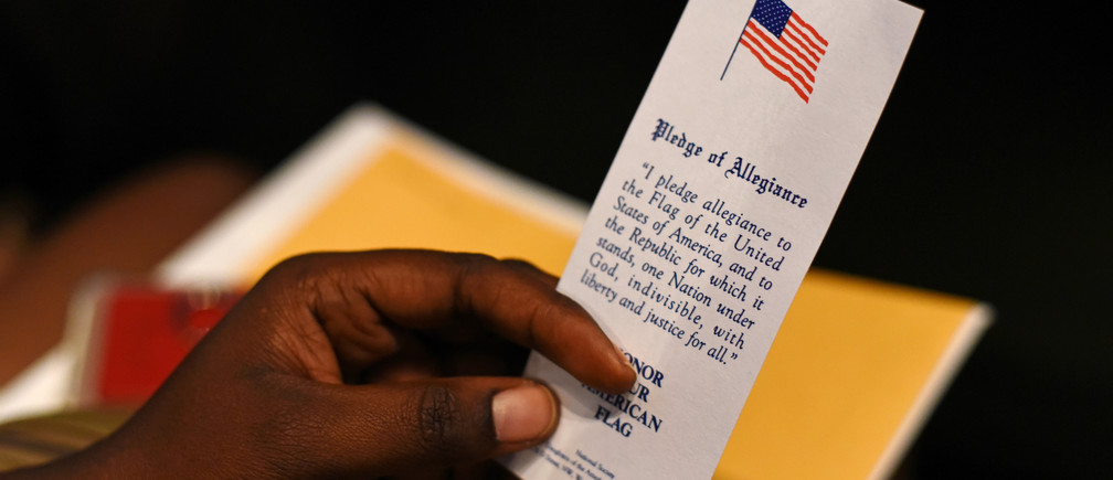 Esther Kamanzi, an immigrant from the Democratic Republic of Congo, holds a copy of the Pledge of Allegiance at her naturalization ceremony in San Antonio, Texas, U.S. June 13, 2019. REUTERS/Callaghan O'Hare politics immigration migrant immigrant migrants people boarders countries democracy capitalism socialism fairness economics government govern administration system power voting votes elections electing faith