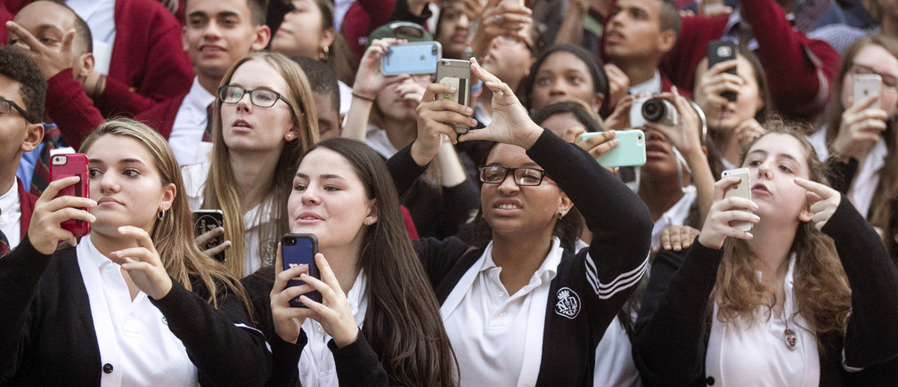 Parochial students from Notre Dame H.S. in the Manhattan, and Cardinal Hayes H. S. and All Hallows H. S. both from the Bronx watch and take photos as Pope Francis arrives at St. Patrick's Cathedral in New York for evening prayer, September 24, 2015. Pope Francis is on a five-day trip to the USA, which includes stops in Washington DC, New York and Philadelphia, after a three-day stay in Cuba.  REUTERS/Aristide Economopoulos | NJ Advance Media/POOL - RTX1SCGK