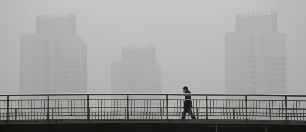 A man wearing a face mask walks on the bund near the financial district of Pudong amid heavy smog in Shanghai, China, December 23, 2015. REUTERS/Aly Song - D1BESCXWGMAB