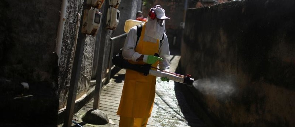 A cleaner disinfects an alley of the Vila Ipiranga slum during the coronavirus disease (COVID-19) outbreak in Niteroi near Rio de Janeiro Brazil, March 25, 2020. REUTERS/Pilar Olivares - RC23RF9KB4P8