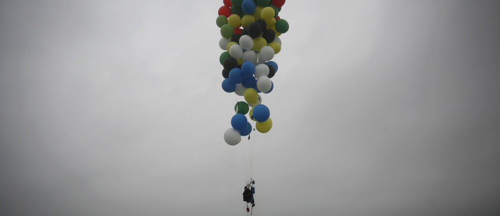 South Africa's Matt Silver-Vallance floats above the sea using helium filled balloons from the airfield of Robben Island across the Atlantic Ocean in Cape Town April 6, 2013. Vallance made the 7 km flight to raise funds and awareness for the Nelson Mandela Children's Hospital. Mandela left hospital on Saturday after more than a week of treatment of pneumonia that raised global concern about the health of the 94-year-old anti-apartheid leader. REUTERS/Mark Wessels (SOUTH AFRICA - Tags: POLITICS SOCIETY TPX IMAGES OF THE DAY) - GM1E9461ULG01