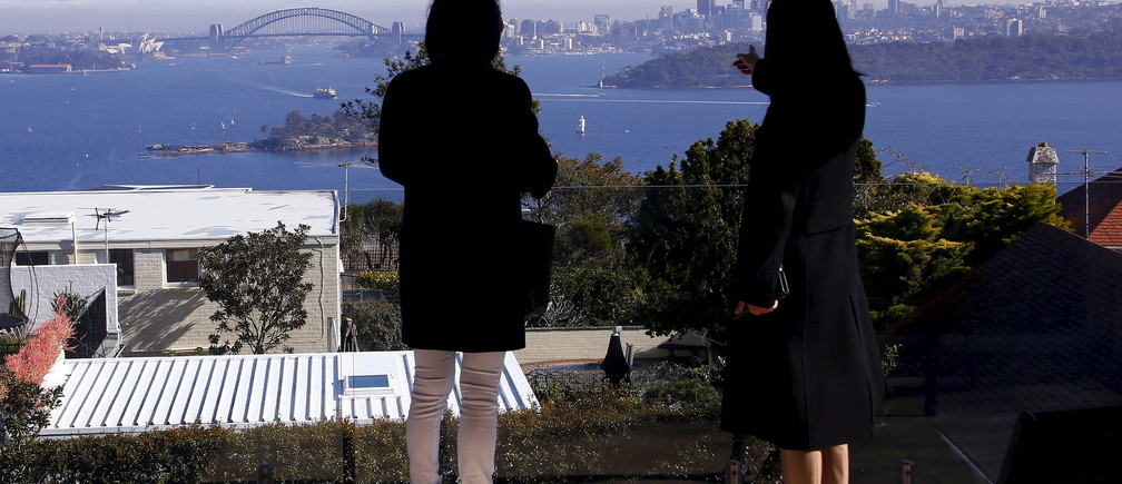 The Sydney Opera House and Harbour Bridge can be seen behind real estate agent LuLu Sun (R) as she escorts Bao Fang, a potential buyer from Shanghai, during an inspection of a property for sale in the Sydney suburb of Vaucluse, Australia, July 11, 2015. Realtors in Australia, Britain and Canada are bracing for a surge of new interest in their already hot property markets, with early signs that wealthy Chinese investors are seeking a safe haven from the turmoil in Shanghai's equity markets. Around 20 percent has been knocked off the value of Chinese shares since mid-June, although attempts by authorities to stem the bleeding are having some effect.   REUTERS/David Gray - RTX1K0JP