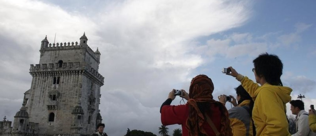 Japanese tourists take pictures in front of Belem Tower in Lisbon November 28, 2008. The global crisis may be pounding bigger travel markets in Europe but it's almost business as usual for Portugal's tourism industry. Cheaper to live in and visit than most of western Europe, the small but diverse Iberian country with sunny beaches, historic sites and some of Europe's finest golf courses has eked out modest growth in tourist numbers so far in 2008, after a record 2007, while others are ebbing. REUTERS/Nacho Doce (PORTUGAL) - GM1E4BT04VX01